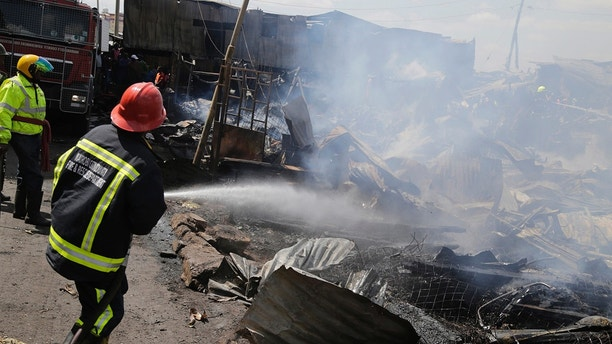 Fire fighters obscured by smoke as they damp down the charred debris after a fire swept through a marketplace in Nairobi, Kenya, Thursday June 28, 2018. Authorities report that several people are known to have died and about 70 are receiving hospital treatment, with rescue teams still searching for more bodies and survivors in the market. (AP Photo/Khalil Senosi)