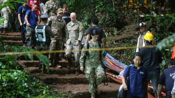 U.S. Special Operations Command Pacific Search and Rescue team personnel walk out of a cave where a young soccer team and their coach are believed to be missing, Thursday, June 28, 2018, in Mae Sai, Chiang Rai province, in northern Thailand. A U.S. military team and British cave experts joined the rescue effort for 12 boys and their soccer coach missing for five days inside the cave being flooded by near-constant rains. (AP Photo/Sakchai Lalit)