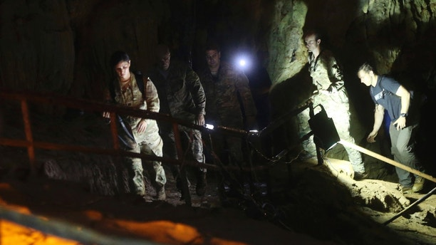 U.S. Special Operations Command Pacific Search and Rescue team personnel walk in a cave where a young soccer team and their coach are believed to be missing, Thursday, June 28, 2018, in Mae Sai, Chiang Rai province, in northern Thailand. A U.S. military team and British cave experts joined the rescue effort for 12 boys and their soccer coach missing for five days inside the cave being flooded by near-constant rains. (AP Photo/Sakchai Lalit)