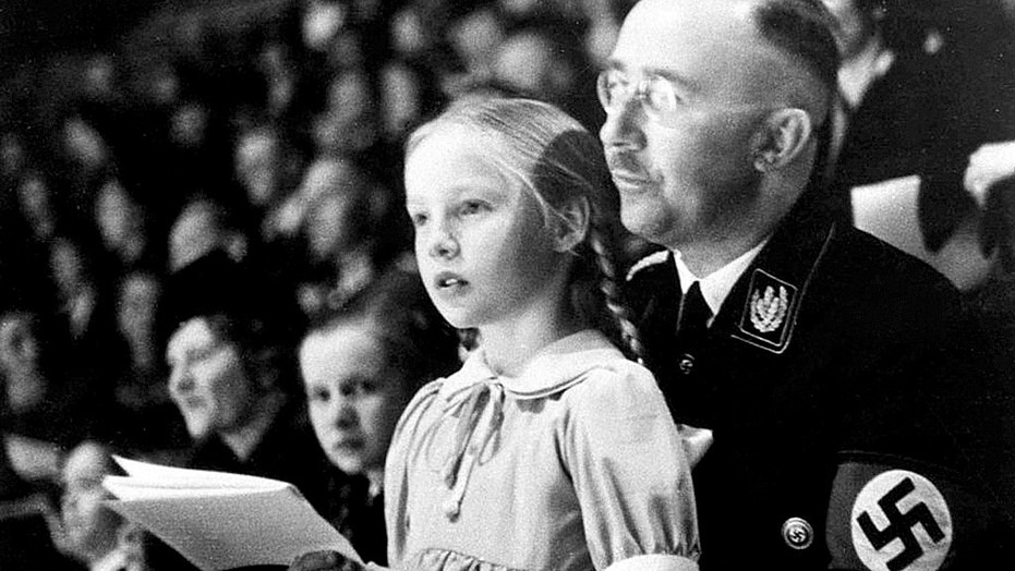 Chief of the German Police and Minister of the Interior Heinrich Himmler, with his daughter Gudrun on his lap, watch an indoor sports display in Berlin, Germany on March 6, 1938. (AP Photo)