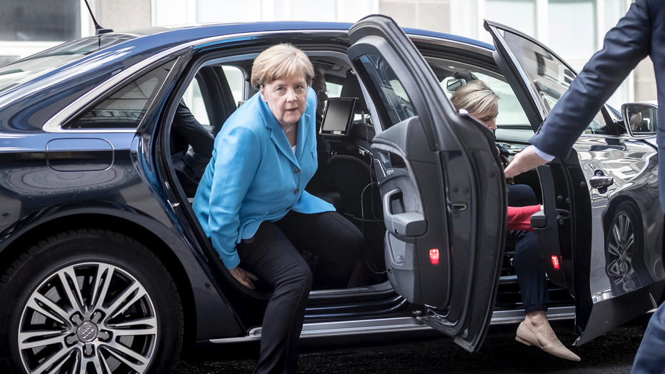 Merkel & Seehofer defuse tensions over immigration policy class=