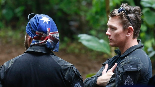 Australian Federal Police and Defense Force personnel talk each other near a cave complex where 12 boys and their soccer coach went missing, in Mae Sai, Chiang Rai province, in northern Thailand, Sunday, July 1, 2018. The frantic effort to locate them in the cave for a week picked up pace as a break in the rain eased flooding in the system of caverns and more experts from around the world joined the anxious rescue mission. (AP Photo/Sakchai Lalit)