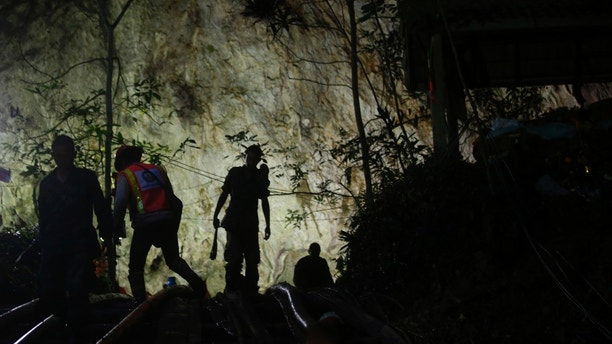 Rescuers make their way down at the entrance to a cave complex where 12 boys and their soccer coach went missing, in Mae Sai, Chiang Rai province, in northern Thailand, Sunday, July 1, 2018. The frantic effort to locate them in the cave for a week picked up pace as a break in the rain eased flooding in the system of caverns and more experts from around the world joined the anxious rescue mission. (AP Photo/Sakchai Lalit)