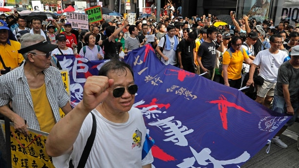 "Protesters carry a banner with Chinese words ""End the one party rule in China"" as thousands of protesters march along a downtown street during an annual pro-democracy protest in Hong Kong Sunday, July 1, 2018. (AP Photo/Vincent Yu)"
