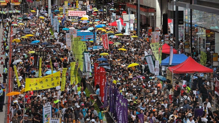 Thousands of protesters march along a downtown street during an annual pro-democracy protest in Hong Kong Sunday, July 1, 2018.