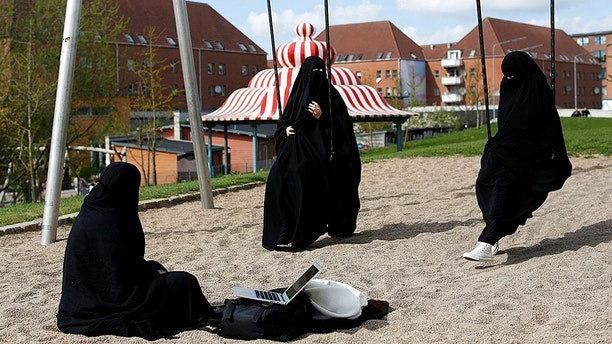 """Zaynab (C) who lives in Mjolnerparken, a housing estate that features on the Danish government's """"Ghetto List"""", sits with her friends Amira and Sabrina in Superkilen, a recently designed urban renewal park that runs beside Mjolnerparken, in Copenhagen, Denmark, May 3, 2018. REUTERS/Andrew Kelly      SEARCH """"DENMARK GHETTO"""" FOR THIS STORY. SEARCH """"WIDER IMAGE"""" FOR ALL STORIES. THE IMAGES SHOULD ONLY BE USED TOGETHER WITH THE STORY - NO STAND-ALONE USES. TPX IMAGES OF THE DAY - RC18146072C0"""