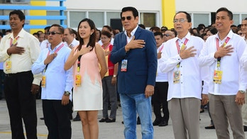 In this handout photo provided by the Tanuan City Information Office, Tanauan city Mayor Antonio Halili, third from right, attends a flag raising ceremony minutes before he was shot outside the municipal hall in Batangas province, south of Manila on Monday, July 2, 2018. Halili, known for parading drug suspects in public but also alleged to have drug ties himself was shot and killed by a sniper Monday in a brazen attack during a flag-raising ceremony in front of hundreds of horrified employees and village leaders. (Tanuan City Information Office via AP)