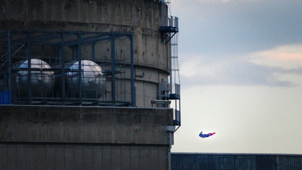 In this photo released by Greenpeace, a drone resembling the character of Superman flies over the nuclear power plant of Le Bugey, central, France, Tuesday, July 3, 2018. The environmental activist group says the drone was harmless but the action showed the lack of security in nuclear installations in France, which is heavily dependent on atomic power. (Nicolas Chauveau/Greenpeace via AP)