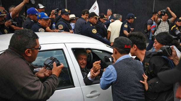 Mexico's President-elect Andres Manuel Lopez Obrador greets a supporter as he leaves the National Palace where he met with Mexico's President Enrique Pena Nieto in Mexico City, Tuesday, July 3, 2018. The president-elect met with the current leader to discuss his transition to office in December, aiming to ensure an orderly transfer of power after a heated and polarizing campaign. (AP Photo/Emilio Espejel)