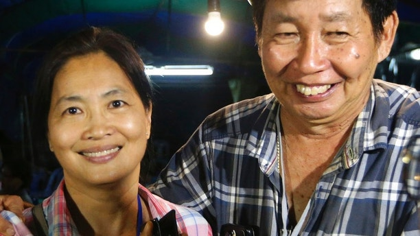 Family members smile after hearing the news that the missing 12 boys and their soccer coach have been found, in Mae Sai, Chiang Rai province, in northern Thailand, Monday, July 2, 2018. A Thai provincial governor says all 12 boys and their coach have been found alive in the cave where they went missing over a week ago in northern Thailand. (AP Photo/Sakchai Lalit)