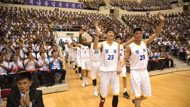 """South and North Korean players of Team Peace wave as they arrive to play in their friendly basketball game at Ryugyong Jong Ju Yong Gymnasium in Pyongyang, North Korea, Wednesday, July 4, 2018. The rival Koreas on Wednesday began two days of friendly basketball games in Pyongyang in their latest goodwill gesture amid a diplomatic push to resolve the nuclear standoff with North Korea. Their uniforms read: """"Peace."""" (Korea Pool via AP)"""