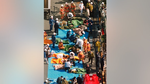 FILE - In this March 20, 1995, file photo, the injured of the deadly gas attack are treated by rescuers near Tsukiji subway station in Tokyo. Japanese media reports say on Friday, July 6, 2018, doomsday cult leader Shoko Asahara, who has been on death row for masterminding the 1995 deadly Tokyo subway gassing and other crimes, has been executed. He was 63. (Kyodo News via AP, File)
