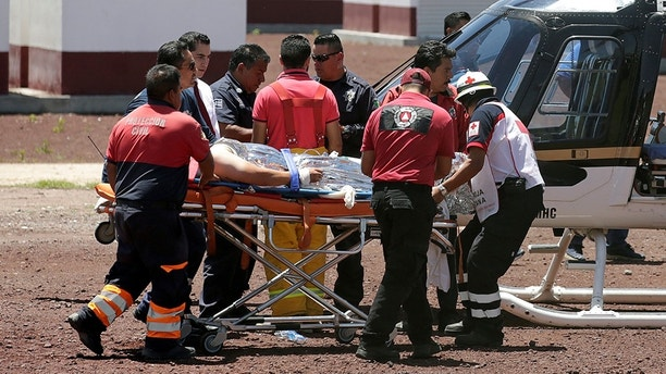 Paramedics wheel a stretcher carrying a man injured due to fireworks explosions toward a helicopter in the municipality of Tultepec, on the outskirts of Mexico City, Mexico July 5, 2018. REUTERS/Daniel Becerril - RC18EC323610