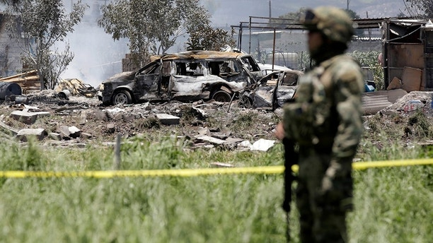 A soldier keeps watch at a site damaged due to fireworks explosions in the municipality of Tultepec, on the outskirts of Mexico City, Mexico July 5, 2018. REUTERS/Daniel Becerril - RC18C0EF5FA0