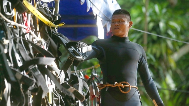 A Thai rescuer hangs his equipment outside a cave where 12 boys and their soccer coach are trapped, in Mae Sai, Chiang Rai province, in northern Thailand, Thursday, July 5, 2018. A Thai official overseeing the rescue operation of the soccer team trapped in the flooded cave said they may not all be extracted at the same time depending on their health. (AP Photo/Sakchai Lalit)