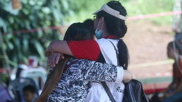 A family member, left, and a Thai official hug each other near a cave where 12 boys and their soccer coach are trapped, in Mae Sai, Chiang Rai province, in northern Thailand, Thursday, July 5, 2018. A Thai official overseeing the rescue operation of the soccer team trapped in the flooded cave said they may not all be extracted at the same time depending on their health. (AP Photo/Sakchai Lalit)