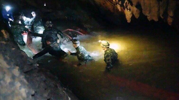 FILE - In this handout photo released by Tham Luang Rescue Operation Center, Thai rescue teams use headlamps to enter a pitch-black cave complex where 12 boys and their soccer coach went missing, in Mae Sai, Chiang Rai province, northern Thailand, Monday, July 2, 2018. The group was discovered late July 2 after 10 days totally cut off from the outside world, and while they are for the most physically healthy, experts say the ordeal has likely taken a mental toll that could worsen the longer the situation lasts. (Tham Luang Rescue Operation Center via AP, File)