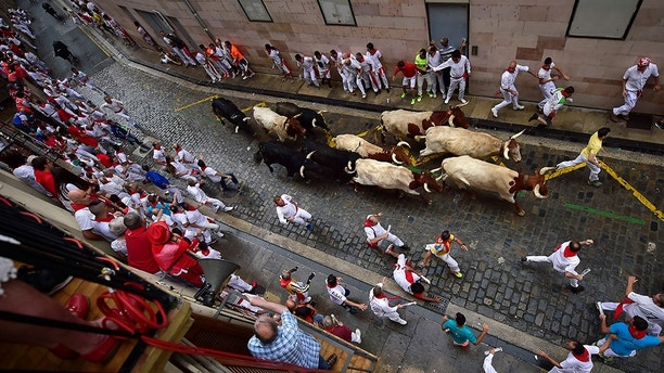 Revellers run next to Puerto de San Lorenzo's fighting bulls during the running of the bulls at the San Fermin Festival, in Pamplona, northern Spain, Saturday, July 7, 2018. Revellers from around the world flock to Pamplona every year to take part in the eight days of the running of the bulls. (AP Photo/Alvaro Barrientos)
