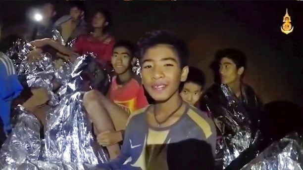 FILE - In this July 3, 2018, file image taken from video provided by the Royal Thai Navy Facebook Page, the boys smile as Thai Navy SEAL medic help injured children inside a cave in Mae Sai, northern Thailand. The group was discovered July 2 after 10 days totally cut off from the outside world, and while they are for the most physically healthy, experts say the ordeal has likely taken a mental toll that could worsen the longer the situation lasts. (Royal Thai Navy Facebook Page via AP, File)