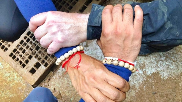 "This undated photo released via the Thailand Navy SEAL Facebook page on Sunday, July 8, 2018, shows rescuers hands locked with a caption reading ""We Thai and the international teams join forces to bring the young Wild Boars home"" where 12 boys and their soccer coach have been trapped since June 23 in a cave in Mae Sai, Chiang Rai province, northern Thailand. The operation has begun to rescue 12 boys and their soccer coach who will need to dive out of the flooded Thai cave where they have been trapped for more than two weeks, with officials saying Sunday morning that ""today is D-Day. (Thailand Navy SEAL Facebook page via AP)"