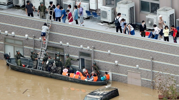 People who are stranded at a flooded hospital are rescued following heavy rain in Kurashiki city, Okayama prefecture, southwestern Japan, Sunday, July 8, 2018. Heavy rainfall hammered southern Japan for the third day, prompting new disaster warnings on Kyushu and Shikoku islands on Sunday. (Shohei Miyano/Kyodo News via AP)