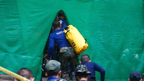 Rescuer arrive near cave where 12 boys and their soccer coach have been trapped since June 23, in Mae Sai, Chiang Rai province, in northern Thailand Sunday, July 8, 2018. Thai authorities are racing to pump out water from the flooded cave before more rains are forecast to hit the northern region. (AP Photo/Sakchai Lalit)