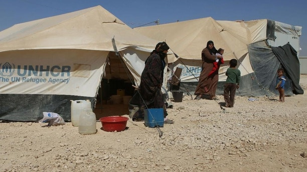 In this Thursday, Oct. 1, 2015 photo, Syrian refugees hang out by their tents at the U.N.-run Zaatari refugee camp near Mafraq, northern Jordan. More than 4 million Syrians fled civil war in their country, now in its fifth year. Most settled in Turkey, Lebanon and Jordan. Banned from working legally, they depend on aid and odd jobs. (AP Photo/Raad Adayleh)