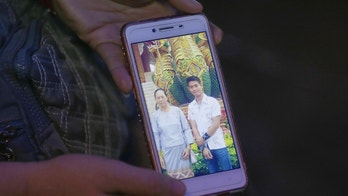 The aunt of coach Ekapol Chantawong shows a picture of the coach and his grandmother on a mobile phone screen, in Mae Sai, Chiang Rai province, in northern Thailand, Wednesday, July 4, 2018. With heavy rains forecast to worsen flooding in a cave in northern Thailand where 12 boys and their soccer coach are waiting to be extracted by rescuers, authorities say they might be forced to have them swim out through a narrow, underwater passage. The 13 are described as healthy and being looked after by medics inside the cave.(AP Photo/Sakchai Lalit)