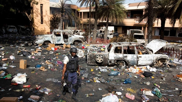 A police officer walks through the parking lot of the Delimart supermarket complex, where vehicles sit charred and looted merchandise lies scattered after two days of protests against a planned hike in fuel prices in Port-au-Prince, Haiti, Sunday, July 8, 2018. Government officials had agreed to reduce subsidies for fuel as part of an assistance package with the International Monetary Fund, but the government suspended the fuel hike after widespread violence broke out. (AP Photo/Dieu Nalio Chery)