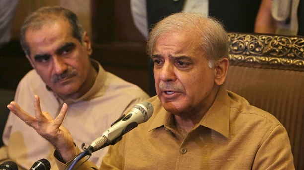 "Shahbaz Sharif, brother of Pakistan's former Prime Minister Nawaz Sharif, who now heads the Pakistan Muslim League, addresses a news conference in Lahore, Pakistan, Thursday, July 12, 2018. Shahbaz Sharif condemned the arrests of their supporters, demanded they stop and that everyone detained be immediately released. He told reporters in Lahore that he plans to be at ""the rally tomorrow to welcome Nawaz Sharif who is returning home with his daughter."" (AP Photo/K.M. Chaudary)"
