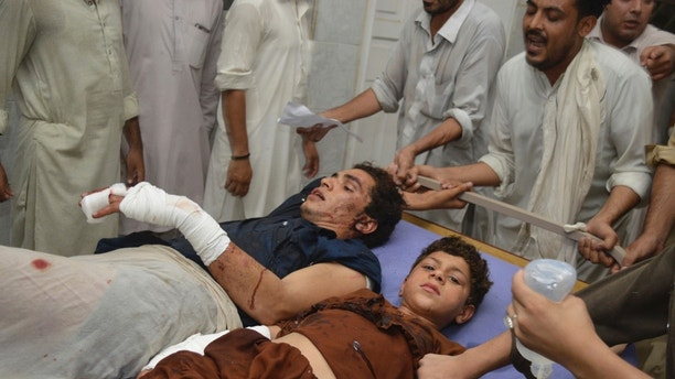 Pakistani blast victims rest at a hospital in Peshawar, Pakistan, Tuesday, July 10, 2018. Police in Pakistan say a suicide bomber has killed a secular party leader and many supporters during an election rally in the northwestern city of Peshawar. (AP Photo/Muhammad Sajjad)