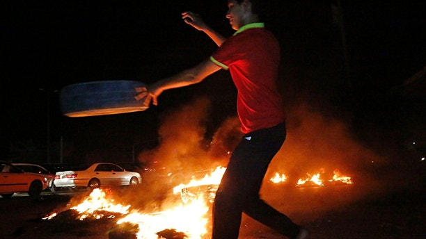 A man burns tires during a protest demanding services and jobs in Basra, 340 miles (550 kilometers) southeast of Baghdad, Iraq, Friday, July 13, 2018. (AP Photo)