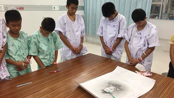 In this photo released by Thailand's Ministry of Health and the Chiang Rai Prachanukroh Hospital, some of the rescued soccer team members bowing their heads respectfully in front of a sketch of the Thai Navy SEAL diver who died while trying to rescue them, Sunday, July 15, 2018, in a hospital in Chiang Rai, northern Thailand. The 12 boys and their soccer coach rescued after being trapped in a flooded cave in northern Thailand are recovering well and are eager to eat their favorite comfort foods after their expected discharge from a hospital next week. (Thailand's Ministry of Health and the Chiang Rai Prachanukroh Hospital via AP)