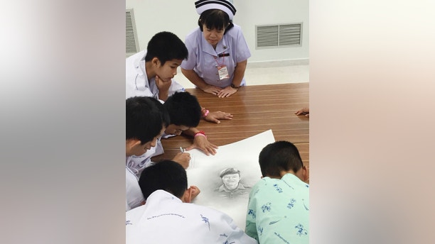 In this photo released by In this photo released by Thailand's Ministry of Health and the Chiang Rai Prachanukroh Hospital, some of the rescued soccer team members autographs and write notes on a sketch of the Thai Navy SEAL diver who died while trying to rescue them, Sunday, July 15, 2018, in a hospital in Chiang Rai, northern Thailand. The 12 boys and their soccer coach rescued after being trapped in a flooded cave in northern Thailand are recovering well and are eager to eat their favorite comfort foods after their expected discharge from a hospital next week. (Thailand's Ministry of Health and the Chiang Rai Prachanukroh Hospital via AP)