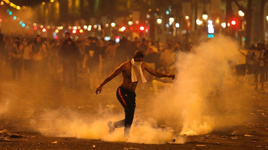 A man kicks a tear gas canister thrown by riot police during clashes on the Champs Elysees avenue where soccer fans were celebrating France's World Cup victory over Croatia.