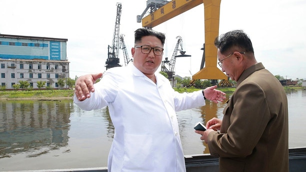 "In this undated photo provided on Tuesday, July 17, 2018, by the North Korean government, North Korean leader Kim Jong Un, left, gestures during his visit to a shipyard in North Hamgyong Province, North Korea. State media say that Kim has harshly reprimanded local officials over a delayed construction project. Independent journalists were not given access to cover the event depicted in this image distributed by the North Korean government. The content of this image is as provided and cannot be independently verified. Korean language watermark on image as provided by source reads: ""KCNA"" which is the abbreviation for Korean Central News Agency. (Korean Central News Agency/Korea News Service via AP)"