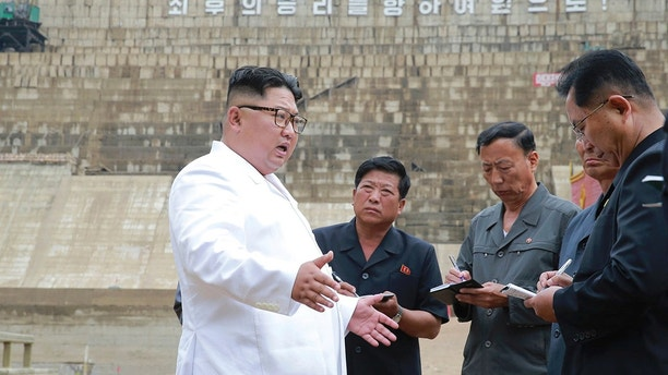 "In this undated photo provided on Tuesday, July 17, 2018, by the North Korean government, North Korean leader Kim Jong Un, left, inspects the construction site of a hydroelectric power plant in North Hamgyong Province, North Korea. State media say that Kim has harshly reprimanded local officials over a delayed construction project. The slogan in the background reads: ""March toward the final victory!"" Independent journalists were not given access to cover the event depicted in this image distributed by the North Korean government. The content of this image is as provided and cannot be independently verified. Korean language watermark on image as provided by source reads: ""KCNA"" which is the abbreviation for Korean Central News Agency. (Korean Central News Agency/Korea News Service via AP)"