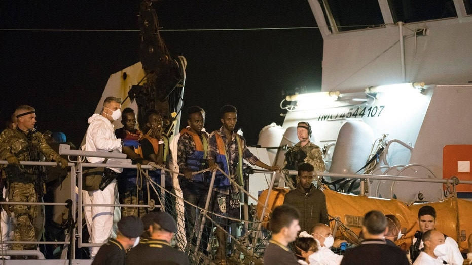 """Migrants desembark from Frontex ship """"Protector"""" at the port of Pozzallo, Sicily, Italy, in the early hours of Monday, July 16, 2018."""