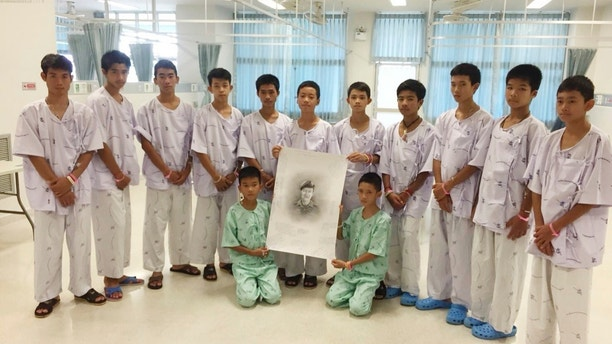 In this photo released by Thailand's Ministry of Health and the Chiang Rai Prachanukroh Hospital, the rescued soccer team members pose with a sketch of the Thai Navy SEAL diver who died while trying to rescue them, Sunday, July 15, 2018, in a hospital in Chiang Rai, northern Thailand. The 12 boys and their soccer coach rescued after being trapped in a flooded cave in northern Thailand are recovering well and are eager to eat their favorite comfort foods after their expected discharge from a hospital next week. (Thailand's Ministry of Health and the Chiang Rai Prachanukroh Hospital via AP)