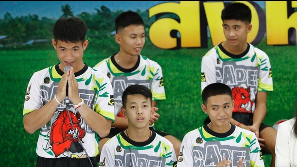 Coach Ekkapol Janthawong, left, and members of the rescued soccer team express their thanks during a press conference discussing their experience of being trapped in a flooded cave, in Chiang Rai, northern Thailand, Wednesday, July 18, 2018. The 12 boys and their soccer coach rescued after being trapped in a flooded cave in northern Thailand are recovering well and are eager to eat their favorite comfort foods after their expected discharge from a hospital soon. (AP Photo/Vincent Thian)