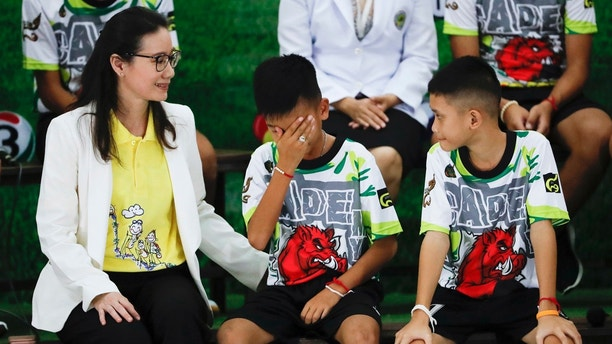 "Rescued soccer player ""Titan"" Chanin Vibulrungruang reacts after paying respect to a portrait of Saman Gunan, the Thai Navy SEAL diver who died in the rescue attempt, during a press conference discussing their ordeal in Chiang Rai, northern Thailand, Wednesday, July 18, 2018. The 12 boys and their soccer coach rescued after being trapped in a flooded cave in northern Thailand are recovering well and are eager to eat their favorite comfort foods after their expected discharge from a hospital soon. (AP Photo/Vincent Thian)"