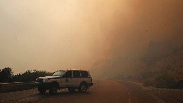 Smoke fills the sky as members of the emergency services block a road near Kineta, west of Athens, Monday, July 23, 2018. Residents were fleeing their homes Monday as a swift-moving fire blazed through a mountainous pine forest west of Athens and churned out smoke that turned the sky orange over the Greek capital. (AP Photo/Thanassis Stavrakis)
