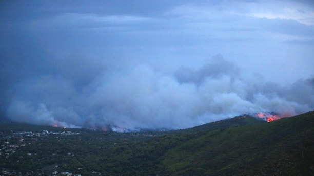Smoke and fire coming the town of Mati, east of Athens, Monday, July 23, 2018. Regional authorities have declared a state of emergency in the eastern and western parts of the greater Athens area as fires fanned by gale-force winds raged through pine forests and seaside settlements on either side of the Greek capital. (AP Photo/Thanassis Stavrakis)
