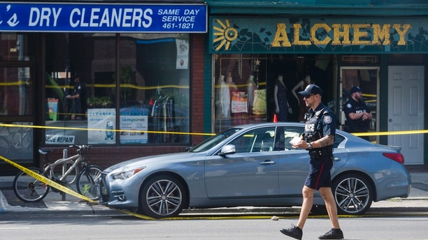 Police are photographed investigating a car with a bullet hole within the scene of a mass shooting in Toronto on Monday, July 23, 2018. (Christopher Katsarov/The Canadian Press via AP)