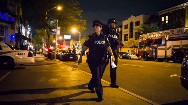Police secure a perimeter around the scene of a mass shooting in Toronto on Monday, July 23, 2018. (Christopher Katsarov/The Canadian Press via AP)
