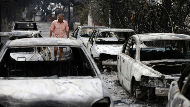 A man passes burned cars in Mati, east of Athens, Tuesday, July 24, 2018. Gale-fanned wildfires raged through holiday resorts near Greece's capital, killing at least 24 people by early Tuesday and injuring more than 100, including 11 in serious condition, in the country's deadliest fire season in more than a decade. (AP Photo/Thanassis Stavrakis)