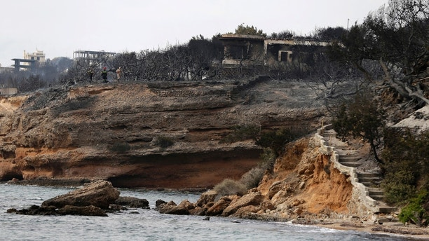 Firefighters stand on a cliff top where burned trees hug the coastline in Mati east of Athens, Tuesday, July 24, 2018. Twin wildfires raging through popular seaside areas near the Greek capital have torched homes, cars and forests and killed at least 49 people, authorities said Tuesday, raising the death toll after rescue crews reported finding the bodies of more than 20 people huddled together near a beach. (AP Photo/Thanassis Stavrakis)