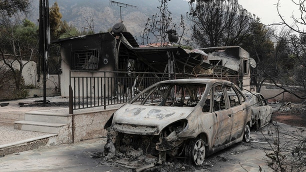 Burnt cars are still in the driveways of destroyed house in Kineta village, west of Athens, Tuesday, July 24, 2018. The death toll from twin wildfires that raged through Greek seaside areas looked set to increase to around 50 Tuesday after rescue crews reported finding the bodies of more than 20 people huddled closely together near a beach northeast of the capital, Athens. (AP Photo/Yorgos Karahalis)