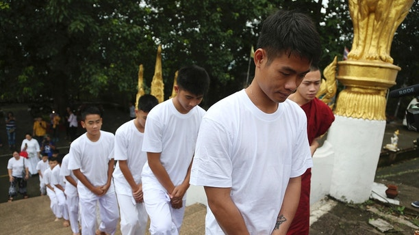 Soccer coach Ekkapol Chantawong, front, and members of the rescued soccer team arrive to attend a Buddhist ceremony that is believed to extend the lives of its attendees as well as ridding them of dangers and misfortunes, in Mae Sai district, Chiang Rai province, northern Thailand, Tuesday, July 24, 2018. The young soccer teammates and their coach who were trapped in a Thai cave have attended a Buddhist ceremony as they prepare to be ordained to become Buddhist novices and monks. (AP Photo/Sakchai Lalit)