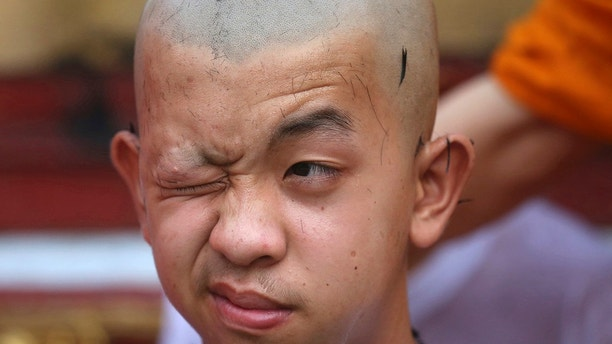 Soccer team member Pornchai Kamluang, his coach, and his teammates who were rescued last week from a flooded cave have their heads shaved in a traditional Buddhist ceremony in Mae Sai district, Chiang Rai province, northern Thailand, Tuesday, July 24, 2018. The young soccer teammates and their coach who have rescued from the cave in northern Thailand took part in a Buddhist ceremony Tuesday as they prepared to be ordained to become Buddhist novices and monks. (AP Photo/Sakchai Lalit)